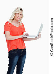 Serious blonde woman holding a laptop in her left hand