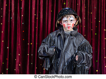 Serious Boy Dressed as Clown Standing on Stage
