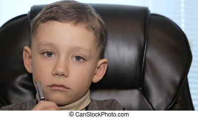 Serious boy in office on armchair, close-up