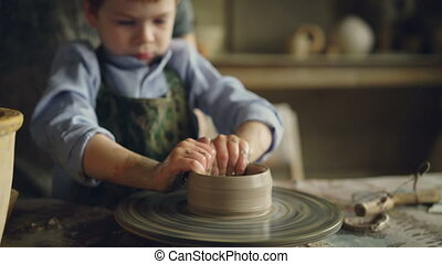 Serious little boy is forming pot from clay on throwing wheel while attending pottery class in children's center. Interesting hobby, happy childhood and pottery concept.