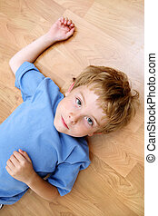 Serious boy lying on the floor