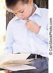 Serious boy reading book