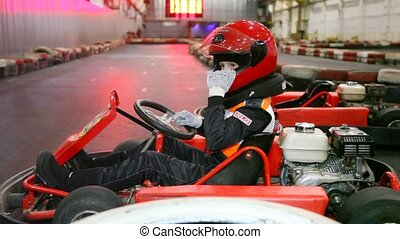 boy sits in go cart and adjust helmet - Serious boy sits in...
