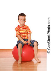 Serious little boy sitting on a gymnastic rubber ball - isolated
