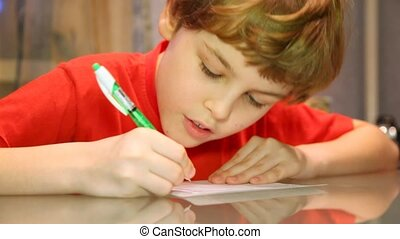 boy writes something very attentively - Serious boy writes...