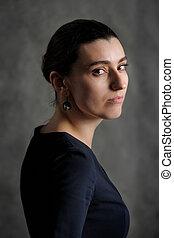 Serious brunette woman in black looking back on dark background