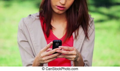 Serious brunette woman texting on her mobile phone in a...