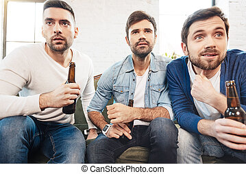 Serious brutal men watching sports games on TV - Male ...