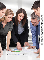 Serious business team having brainstorm in modern office. Adult attractive business woman leading group of business people