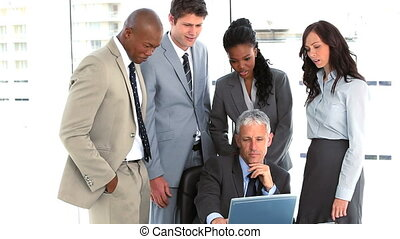 Serious business team surrounding their manager in a bright...