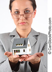 business woman in glasses holds model of house