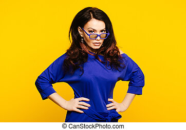 serious business woman in glasses on yellow background