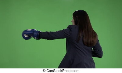 Serious business woman with boxing gloves punching against green screen