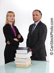 serious businessman and businesswoman posing next to pile of...