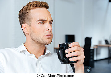 Serious businessman drinking coffee in offiice