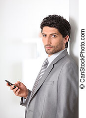 Serious businessman holding a mobile phone