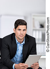 Serious businessman holding a tablet