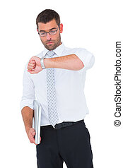 Serious businessman holding laptop checking time