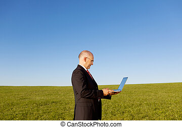 Serious Businessman Holding Laptop On Field