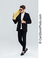 Serious businessman in sunglasses holding yellow skateboard on his sholder