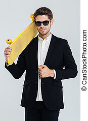 Serious businessman in sunglasses holding yellow skateboard on his shoulder