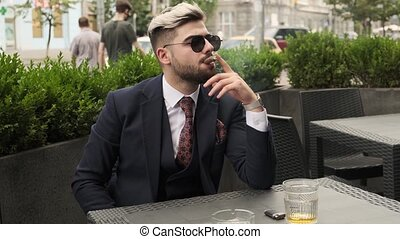 Serious businessman smoking cigar and drinking scotch or whiskey in restaurant terrace, elite mens club outdoor. relaxing time. man crushes cigar ash