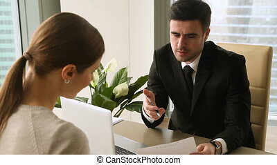 Serious businessman interviewing young female applicant,...