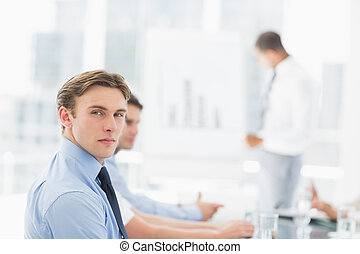 Serious businessman looking at camera during a meeting