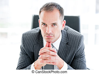 Serious businessman looking at the camera sitting