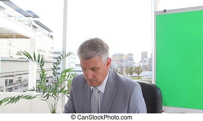 Serious businessman making a phone call in an office