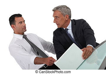 Serious businessman pointing at a colleague's laptop