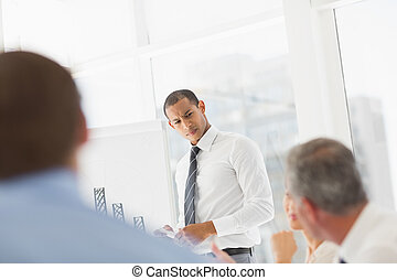 Serious businessman presenting bar chart to co workers