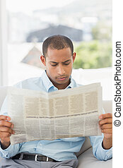 Serious businessman reading newspaper on the couch