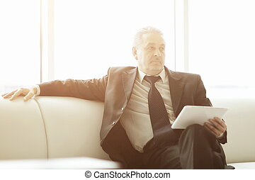 serious businessman reading text on a digital tablet