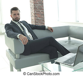 businessman sitting in the lobby of a modern office.