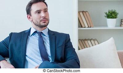 Serious businessman sitting on the sofa