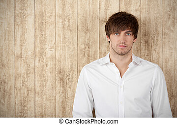 Serious Businessman Standing Against Wooden Wall