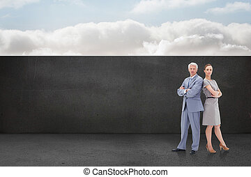 Serious businessman standing back to back with a woman against balcony and bright sky