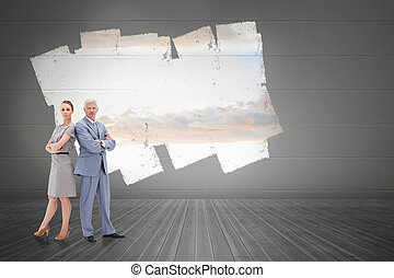 Serious businessman standing back to back with a woman  against display on wall showing bright sky