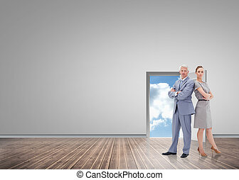 Serious businessman standing back to back with a woman against door opening showing blue sky