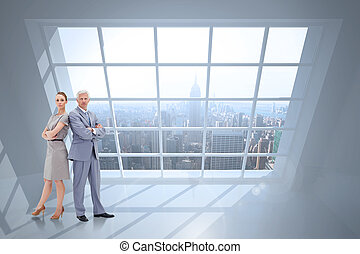 Serious businessman standing back to back with a woman against room with large window showing city