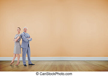 Serious businessman standing back to back with a woman against room with wooden floor