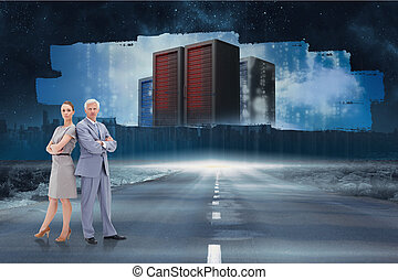 Serious businessman standing back to back with a woman against screen showing server towers