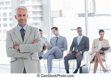 Serious businessman standing in a waiting room with business...