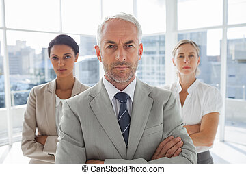Serious businessman standing in fro
