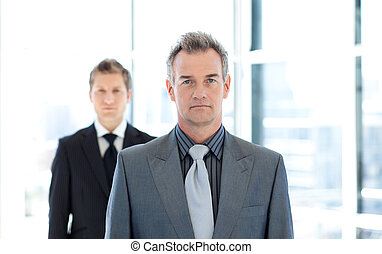Serious businessman standing in front of the camera