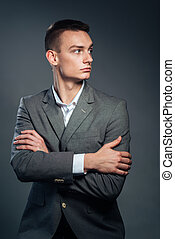 Serious businessman standing with arms folded