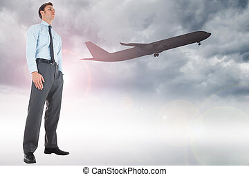 Serious businessman standing with hand in pocket against airplane flying over clouds
