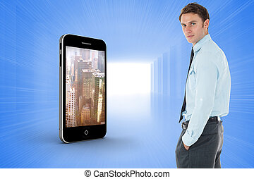 Serious businessman standing with hands in pockets against bright blue room
