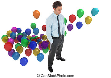 Serious businessman standing with hands in pockets against colourful balloons